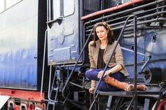 在一辆老蒸汽机车附近的美丽的妇女 免版税库存照片