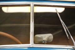 在一辆老经典汽车的方向盘的挡风玻璃和零件的特写镜头 库存照片