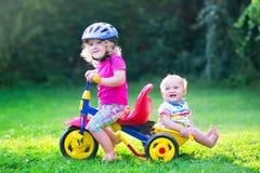 在一辆自行车的两个孩子在庭院里 免版税图库摄影