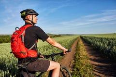 在一辆自行车的年轻人骑马在有背包的绿色草甸 免版税图库摄影
