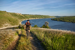 在一辆自行车的年轻人骑马在有背包的绿色草甸 库存图片
