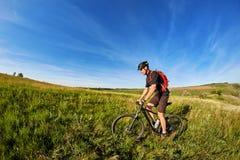 在一辆自行车的年轻人骑马在有背包的绿色草甸 免版税库存图片