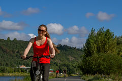 在一辆自行车的美好的少妇骑马在散步 库存图片