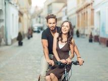 在一辆自行车的美好的年轻夫妇在城市 库存照片