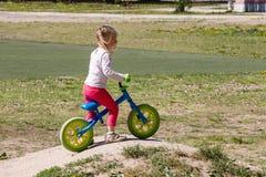 在一辆跑的自行车的逗人喜爱的学龄前女孩骑马在夏天 免版税库存图片