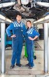 在一辆车下的两位汽车修理师在一辆水力汽车举 免版税库存照片