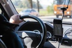 在一辆驾驶的汽车的方向盘的司机的手 免版税库存图片