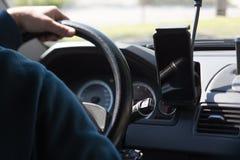 在一辆驾驶的汽车的方向盘的司机的手 免版税库存照片