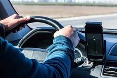 在一辆驾驶的汽车的方向盘的司机的手 免版税图库摄影