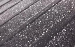 在一辆黑汽车的雪花作为背景 库存图片