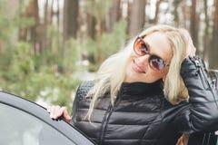 在一辆黑汽车附近的年轻可爱的妇女 库存照片