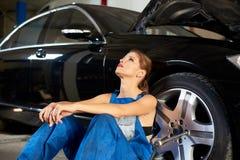 在一辆黑汽车附近的诱人的女孩在修理车库 库存照片