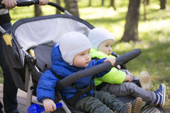 在一辆婴儿推车的两男孩孪生在街道 库存照片