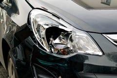 在一辆黑汽车的残破的前灯 库存照片