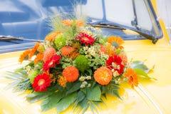 在一辆黄色婚礼汽车的新娘花束 免版税图库摄影