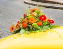 在一辆黄色婚礼汽车的新娘花束 免版税库存图片