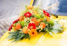 在一辆黄色婚礼汽车的新娘花束 免版税库存照片