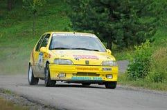 在一辆黄色葡萄酒标致汽车105赛车的未认出的司机 免版税库存图片