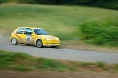 在一辆黄色葡萄酒标致汽车105赛车的未认出的司机 库存照片