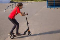 在一辆cick滑行车的逗人喜爱的年轻嬉戏女孩骑马在skatepark 免版税库存图片