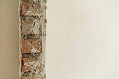 在一边涂灰泥的砖墙 库存照片