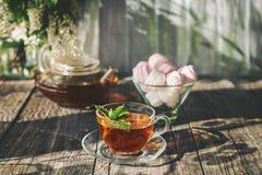 在一透明玻璃茶壶和杯的可口草莓绿色薄菏茶在夏天,在一张土气木桌上用蛋白软糖 免版税库存图片