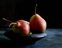 在一金属片的三个成熟水多的梨在黑暗的背景 图库摄影