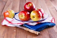 在一金属片的红色有机苹果在木背景 免版税库存图片
