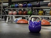 在一间健身房的Kettlebell与在背景的更加五颜六色的kettlebells 免版税图库摄影