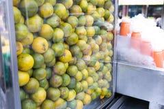 在一间陈列室的成熟蜜桔桔子做的汁液在轰隆Lampu市场,曼谷,泰国上 库存图片