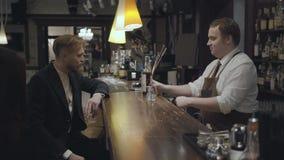 在一间高级餐馆或客栈的酒吧的后一个老练的侍者身分为年轻提供好类威士忌酒 股票视频