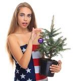 在一面美国国旗包裹的女孩隔绝在与一棵杉树的白色背景在手上 免版税库存图片
