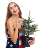 在一面美国国旗包裹的女孩隔绝在与一棵杉树的白色背景在手上 库存图片
