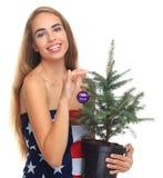在一面美国国旗包裹的女孩隔绝在与一棵杉树的白色背景在手上 免版税库存照片
