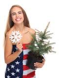 在一面美国国旗包裹的女孩隔绝在与圣诞树的白色背景和雪花在她的手上 库存照片