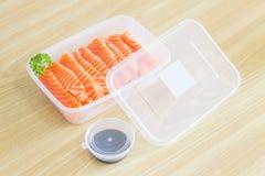 在一顿塑料盒容器准备服务膳食里面的三文鱼生鱼片用在塑料杯子容器的酱油 准备好去斑鳟属 免版税库存照片