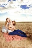 在一顿野餐的家庭在海滩 母亲、父亲和婴孩在Th附近 免版税库存照片