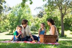 在一顿野餐的愉快的家庭在公园 免版税图库摄影