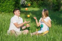 在一顿野餐的年轻夫妇在城市停放 库存图片
