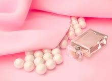 在一颗玻璃瓶和珍珠的香水在桃红色丝绸成串珠状 库存照片