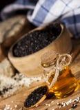 在一颗玻璃瓶和白色和黑种子的新鲜的麻油在木碗 免版税库存图片