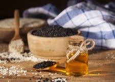 在一颗玻璃瓶和白色和黑种子的新鲜的麻油在木碗 库存图片