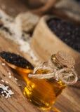 在一颗玻璃瓶和白色和黑种子的新鲜的麻油在木碗 库存照片