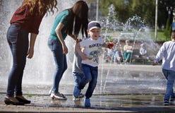 在一飞溅的fontain附近的孩子在镇的中心 免版税图库摄影