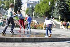 在一飞溅的fontain附近的孩子在镇的中心 免版税库存照片