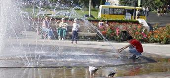 在一飞溅的fontain附近的孩子在镇的中心 免版税库存图片