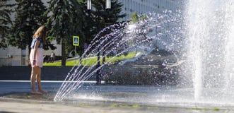 在一飞溅的fontain附近的孩子在镇的中心 库存照片