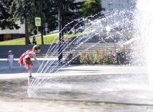 在一飞溅的fontain附近的孩子在镇的中心 图库摄影