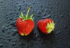 在一黑暗的背景wate的两个大成熟红色草莓莓果 库存图片