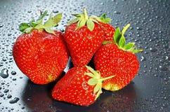 在一黑暗的背景wate的五个大成熟红色草莓莓果 库存照片